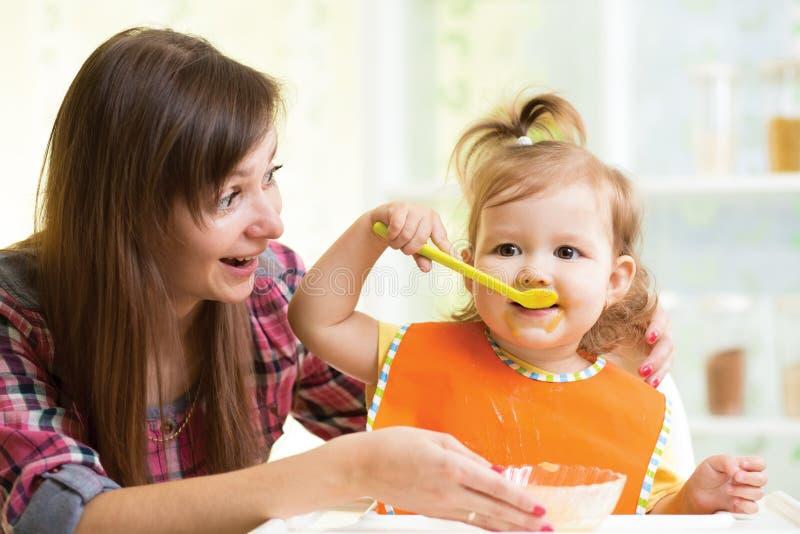吃与匙子的孩子女孩户内 免版税库存图片