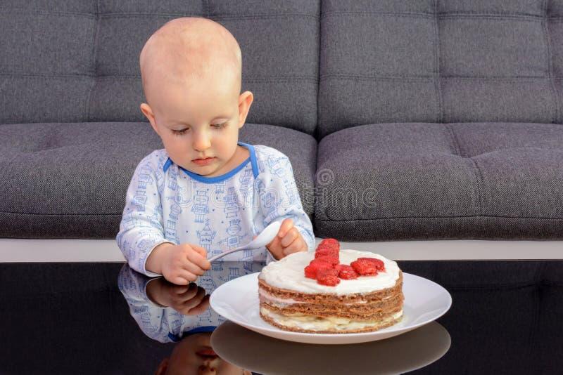 吃与匙子的小男孩生日蛋糕,生日快乐 库存图片