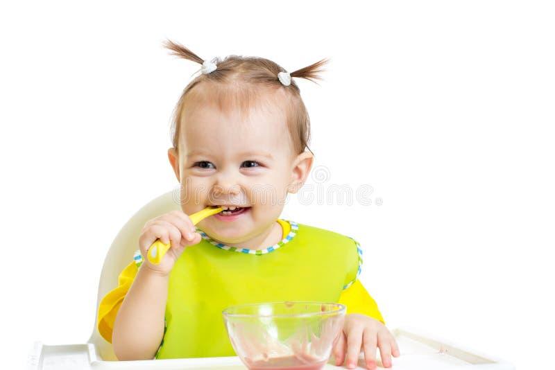 吃与匙子的愉快的婴孩坐在桌上 免版税库存图片
