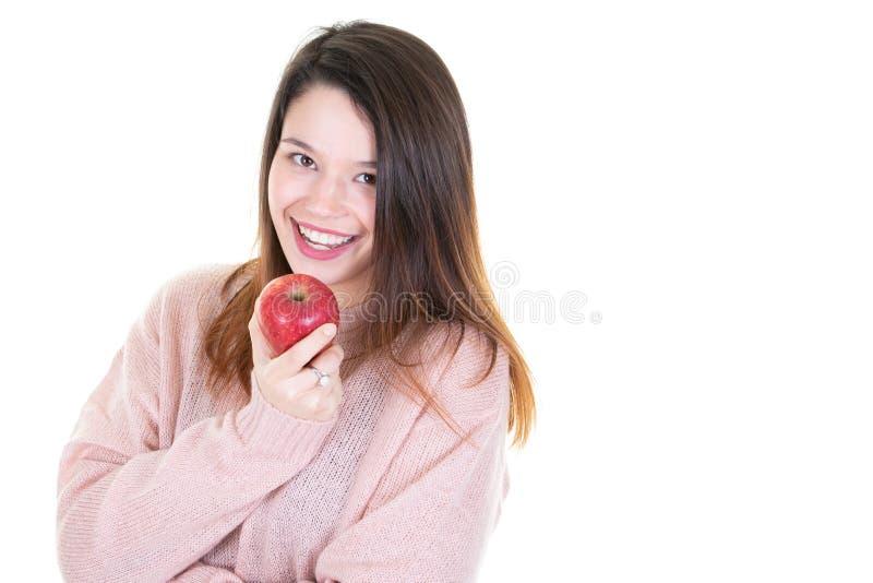 吃与后面拷贝空间的快乐的年轻女人画象红色苹果 库存照片