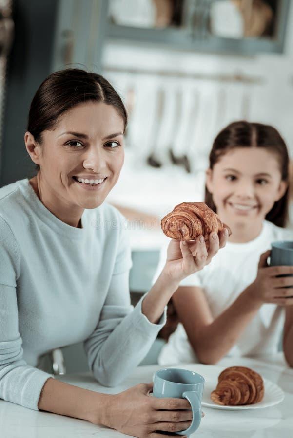 吃与她的女儿的花姑娘新月形面包 图库摄影
