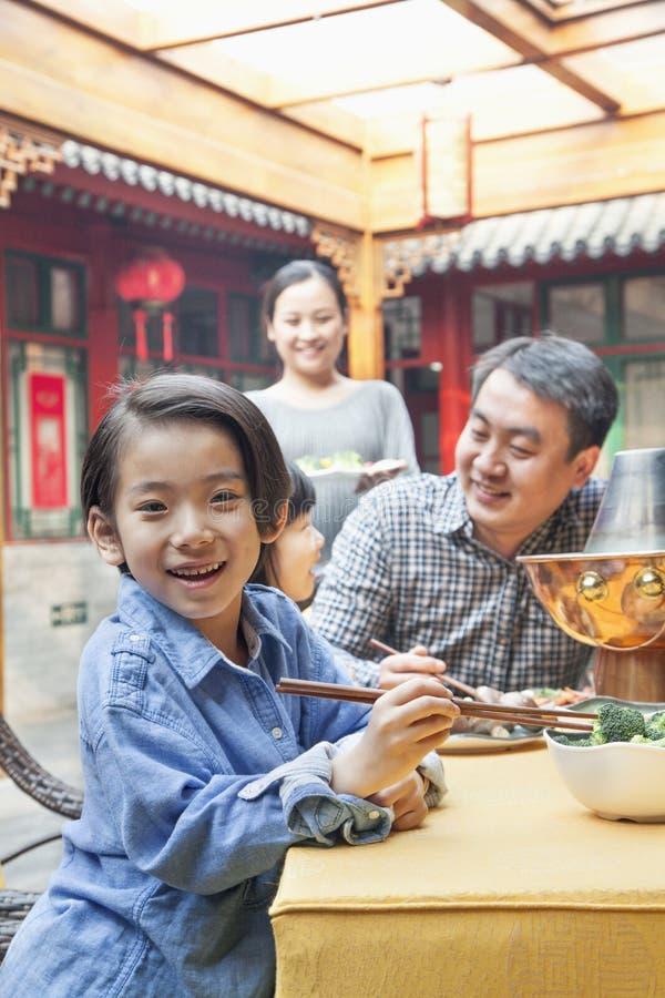 吃与她的家庭的小女孩画象晚餐 免版税图库摄影