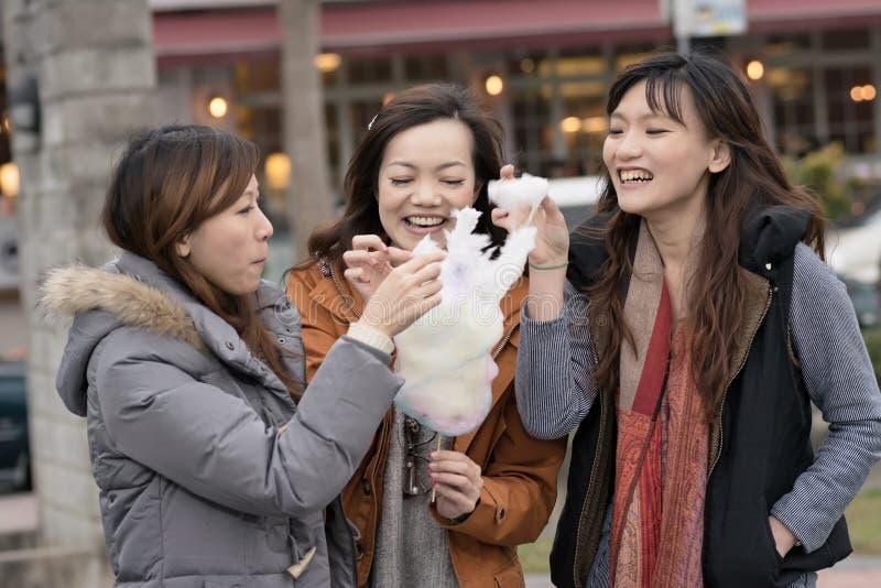 吃与她的朋友的愉快的年轻亚裔妇女棉花糖 库存图片
