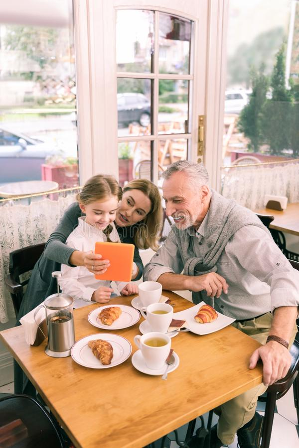 吃与孙女的愉快的放光的祖父母早晨新月形面包 免版税库存图片