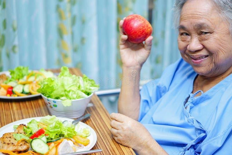 吃与希望和愉快的一会儿的亚裔资深或年长老妇人妇女患者早餐健康食品和饥饿坐床 库存照片