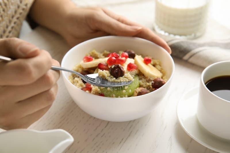 吃与榛子、猕猴桃、香蕉和石榴种子的妇女奎奴亚藜粥在白色木桌上 免版税库存图片