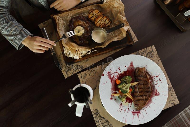 吃与菜的妇女肉牛排在餐馆 在猪纵向时间白色的背景滑稽的几内亚午餐 一顿健康晚餐的概念 饭桌的顶视图 库存照片