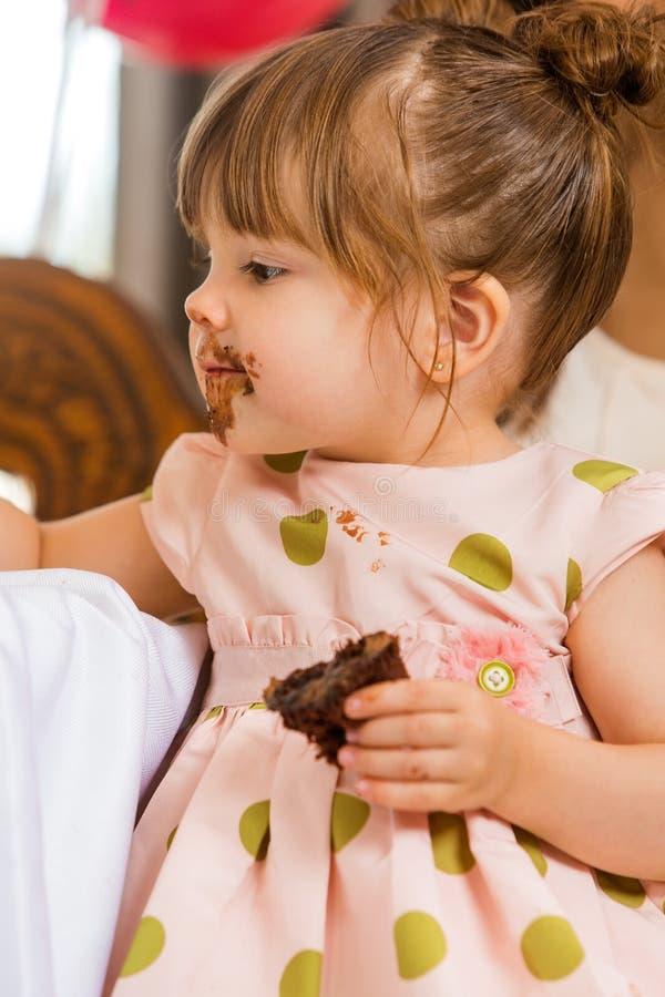 吃与结冰的女孩蛋糕在她的面孔 库存照片