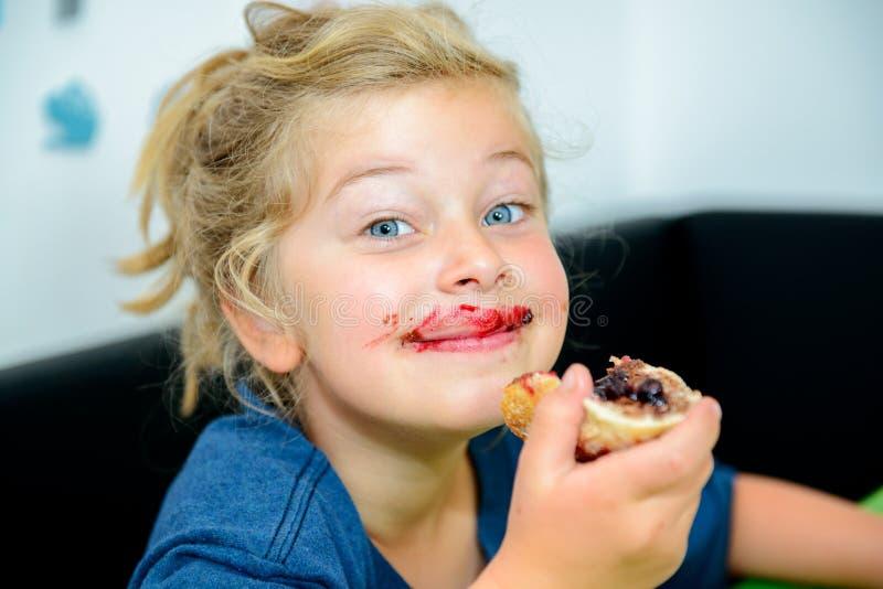 吃与marmelade的滑稽的女孩小圆面包 免版税库存图片