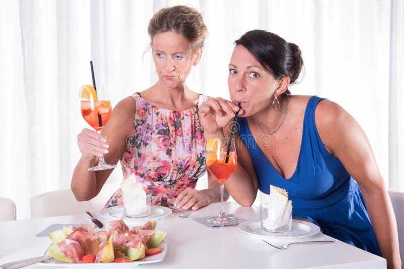 吃两名可爱的妇女轻的晚餐 免版税库存照片