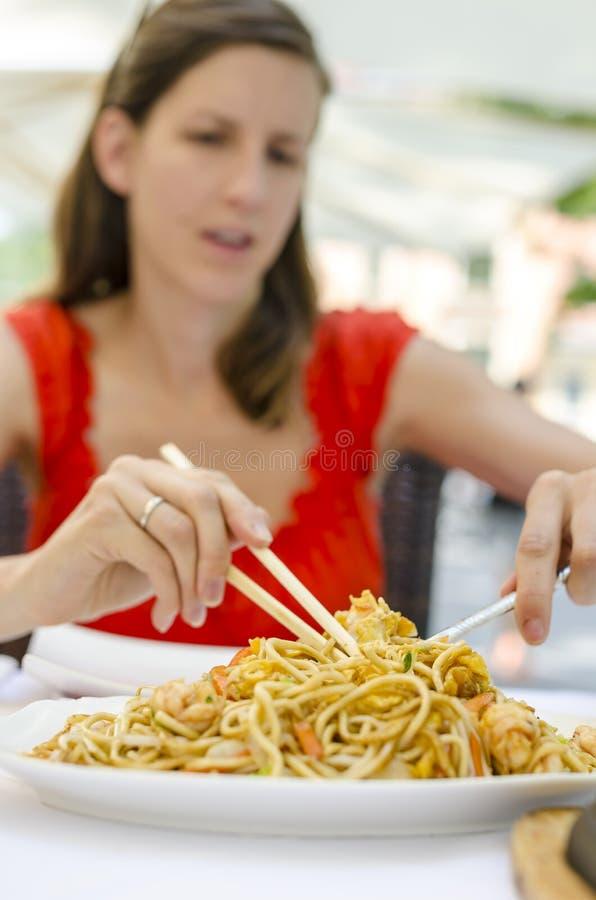 吃中国面条的少妇 免版税图库摄影