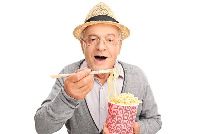 吃中国食物用棍子的资深绅士 库存照片