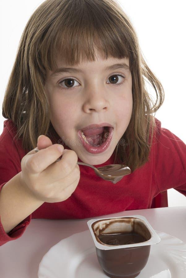 吃乳蛋糕的小女孩 免版税库存图片