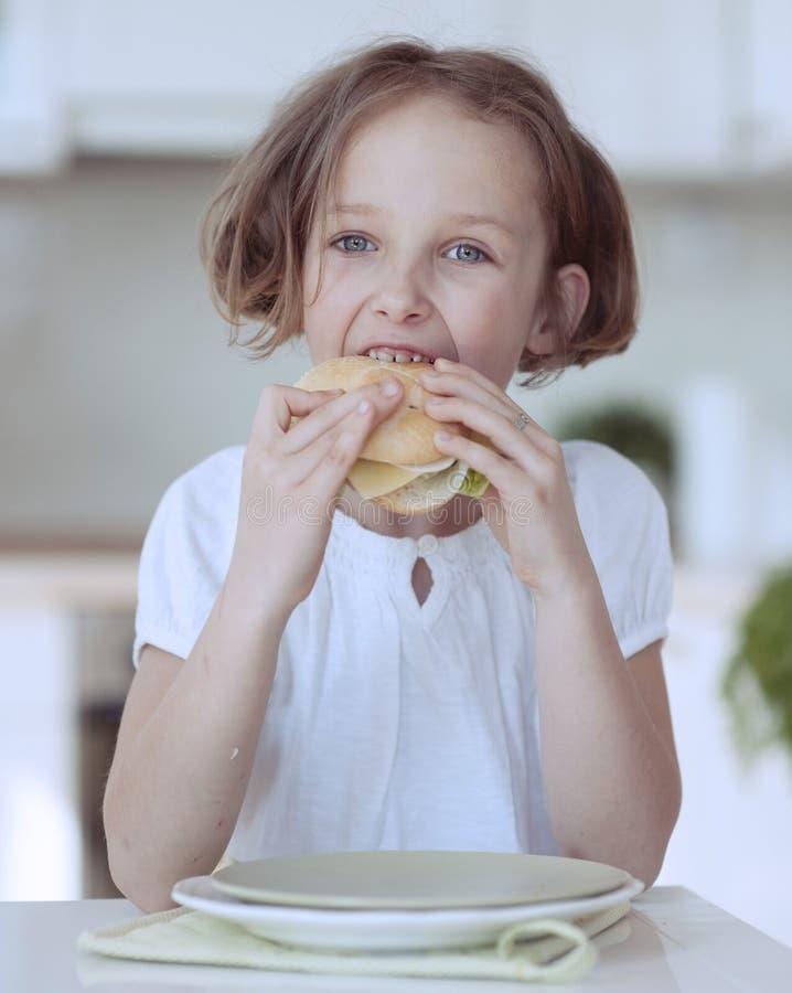 吃乳酪三明治的女孩 库存照片