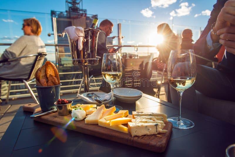 吃乳酪和喝酒的人们在屋顶餐馆在日落时间 库存照片
