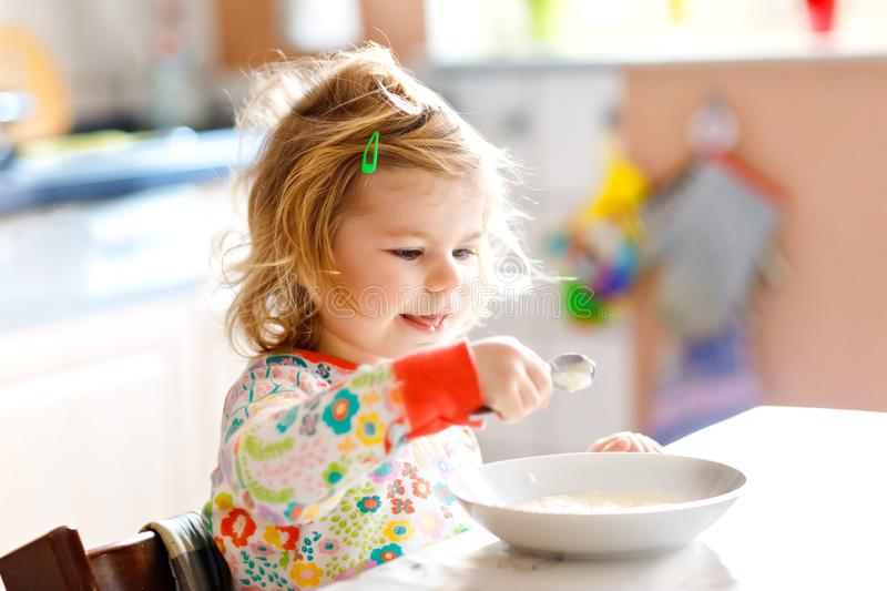 吃从匙子的可爱的小孩女孩健康porrige五颜六色睡衣坐的早餐逗人喜爱的愉快的小孩子的 免版税库存照片
