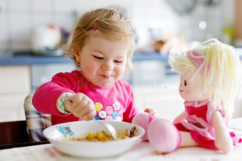 吃从叉子菜和面团的可爱的女婴 一点喂小孩和使用与玩具玩偶 逗人喜爱的小孩 免版税库存照片