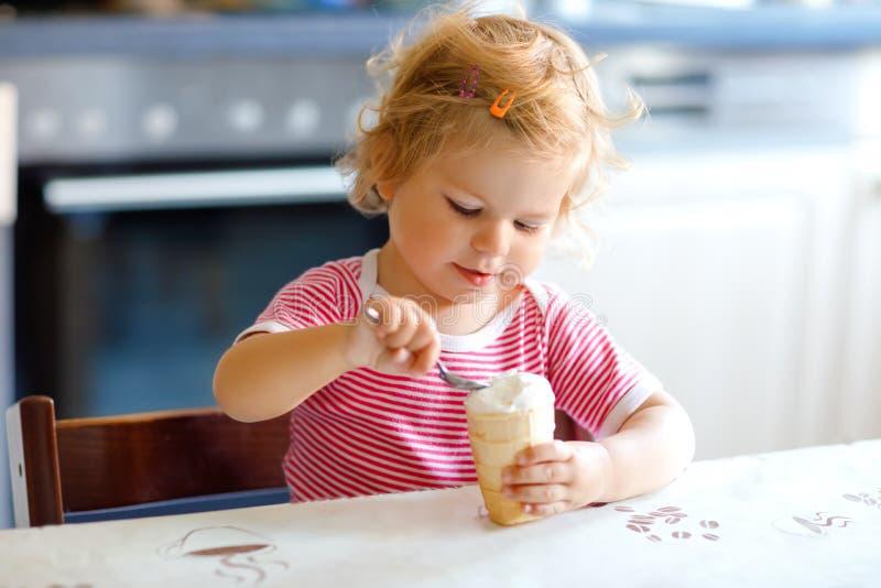 吃从在奶蛋烘饼锥体的匙子甜冰淇淋的可爱的女婴 食物,儿童,哺养和发展概念 逗人喜爱 库存照片