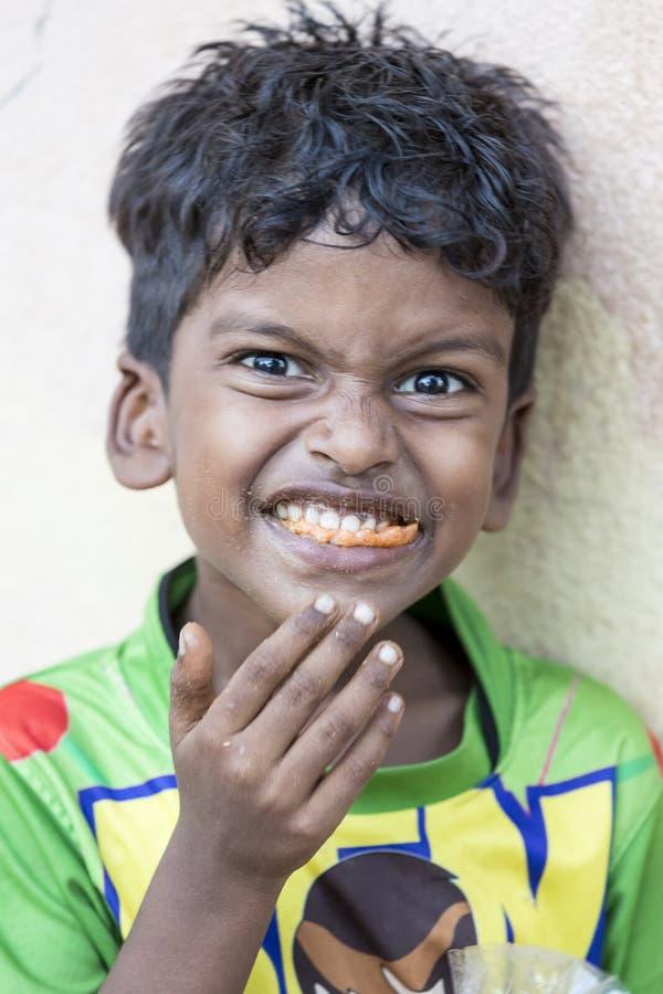 吃他的在街道的未认出的可怜的印地安男孩画象快餐 免版税库存图片