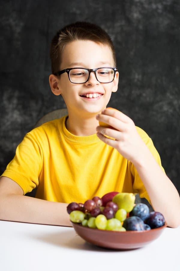 吃他的快餐的十几岁的男孩果子 免版税库存照片