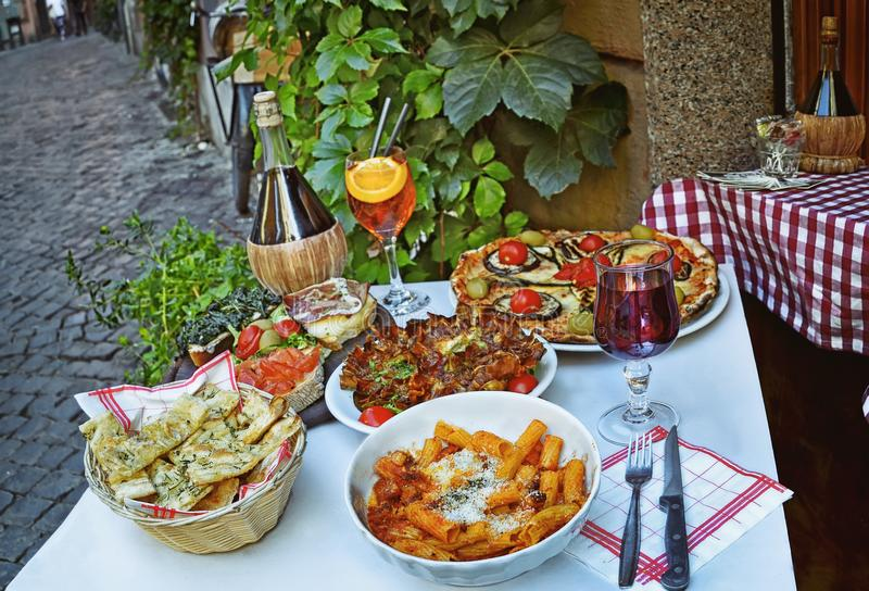 吃传统意大利食物的未认出的人民在室外餐馆在Trastevere区 免版税库存图片