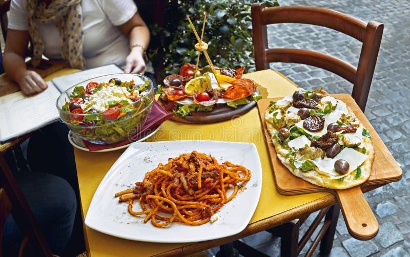 吃传统意大利食物的未认出的人民在室外餐馆 库存图片
