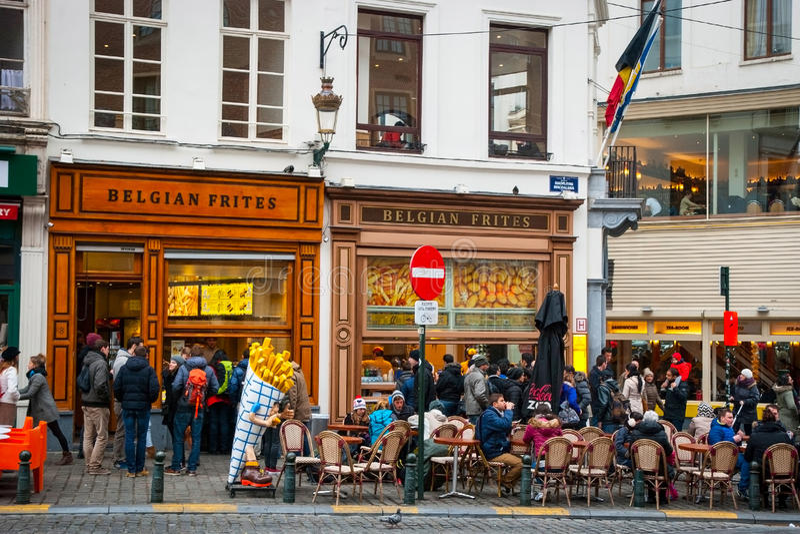 吃传统比利时frites的人们在布鲁塞尔 免版税库存照片