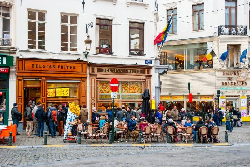 吃传统比利时frites的人们在布鲁塞尔 免版税库存图片
