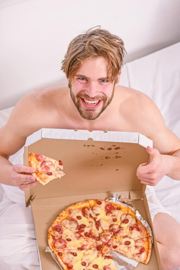 吃低贱食物早餐的人有胡子的帅哥在床上 人喜欢早餐饥饿的年轻人的比萨  库存照片
