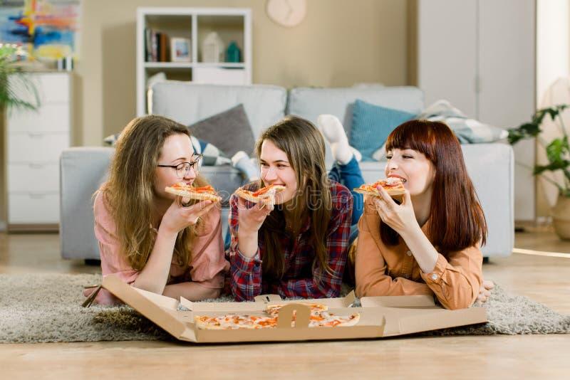 吃便当 笑愉快的三个美丽的朋友,在家吃比萨党 吃的妇女晚餐一起 免版税库存照片