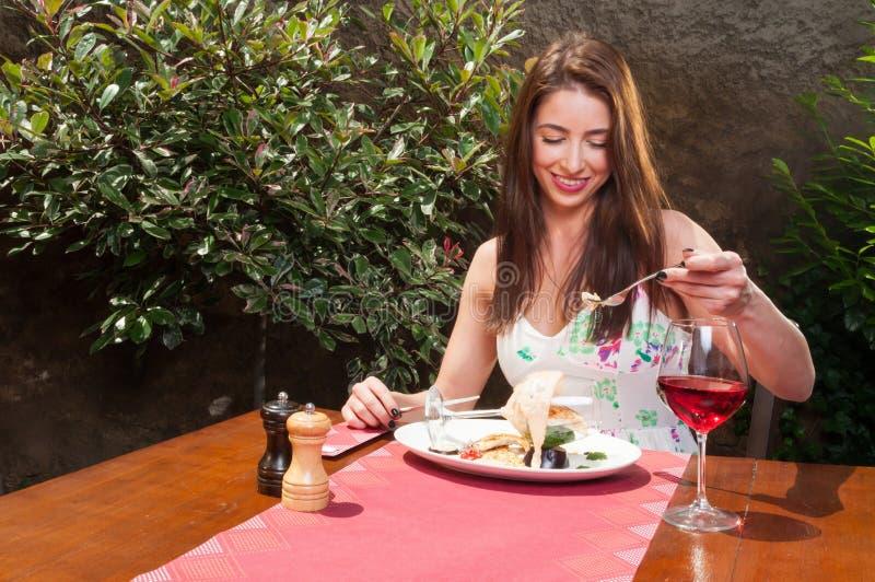 吃俏丽的夫人在大阳台的花梢午餐 免版税库存图片