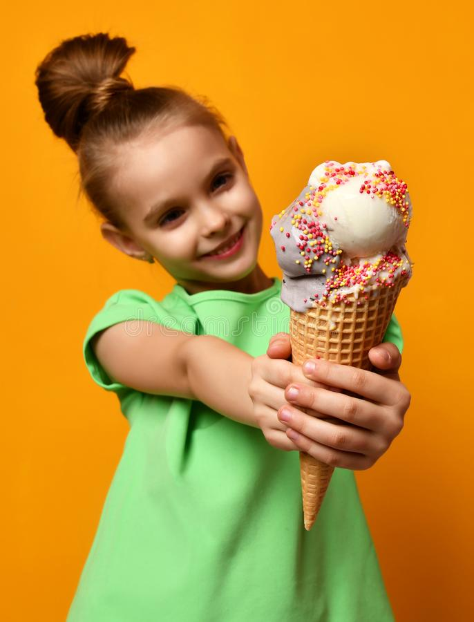 吃俏丽的女婴的孩子舔香蕉和巧克力冰淇凌在奶蛋烘饼锥体 免版税库存照片