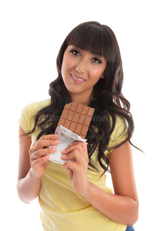 吃俏丽的妇女年轻人的巧克力 免版税图库摄影