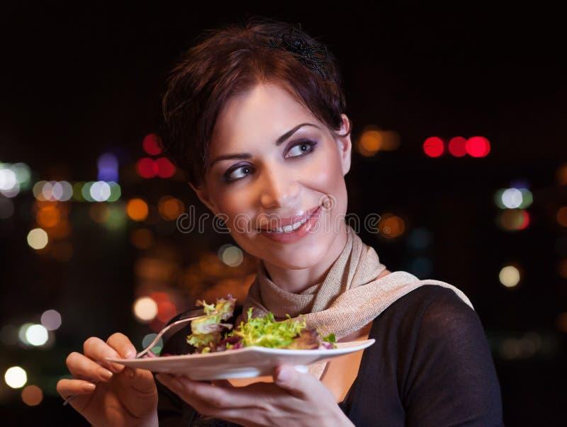 吃俏丽的妇女晚餐 免版税库存图片