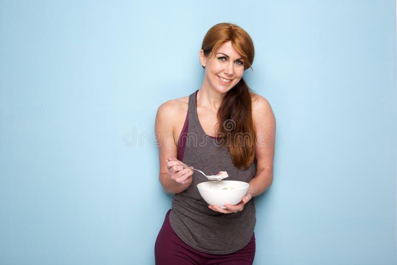 吃健康早餐的健身妇女 免版税库存图片