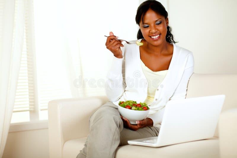 吃健康沙拉的可爱的少妇 免版税库存图片