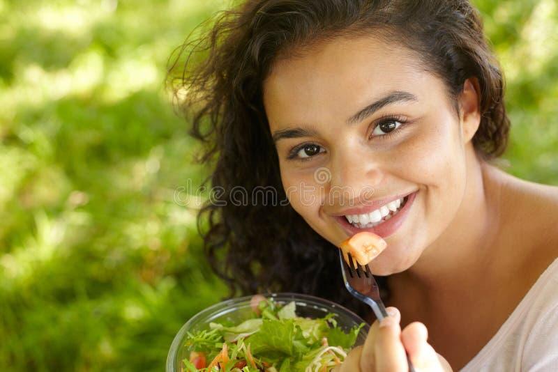 吃健康沙拉的少妇户外 免版税图库摄影