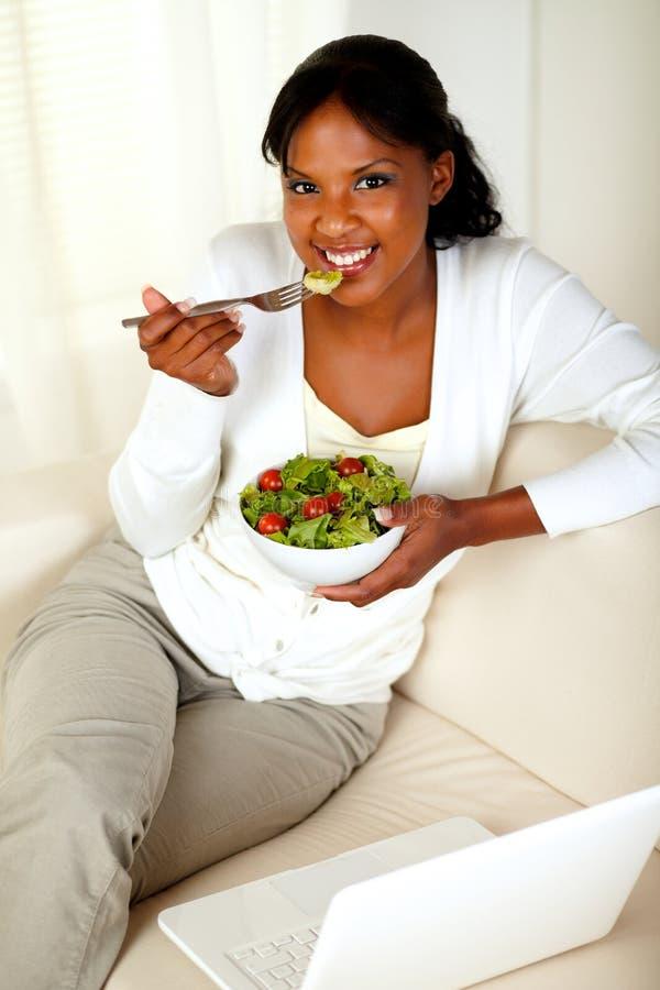 吃健康沙拉的新女性查看您 免版税图库摄影