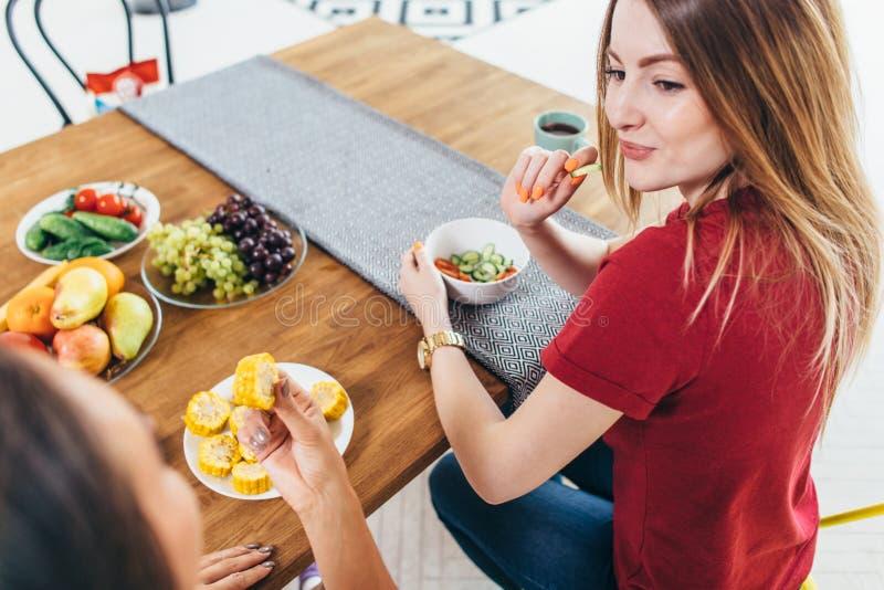 吃健康沙拉的美丽的适合妇女在厨房里 免版税库存图片