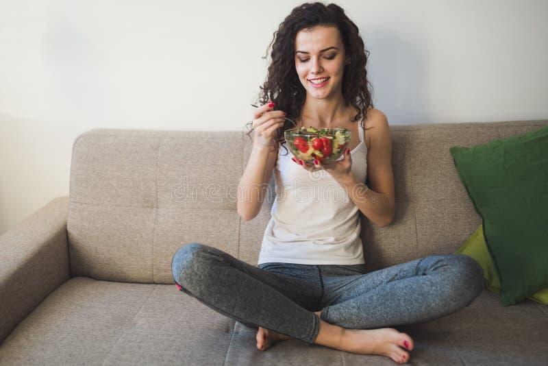 吃健康沙拉的美丽的适合妇女 库存照片