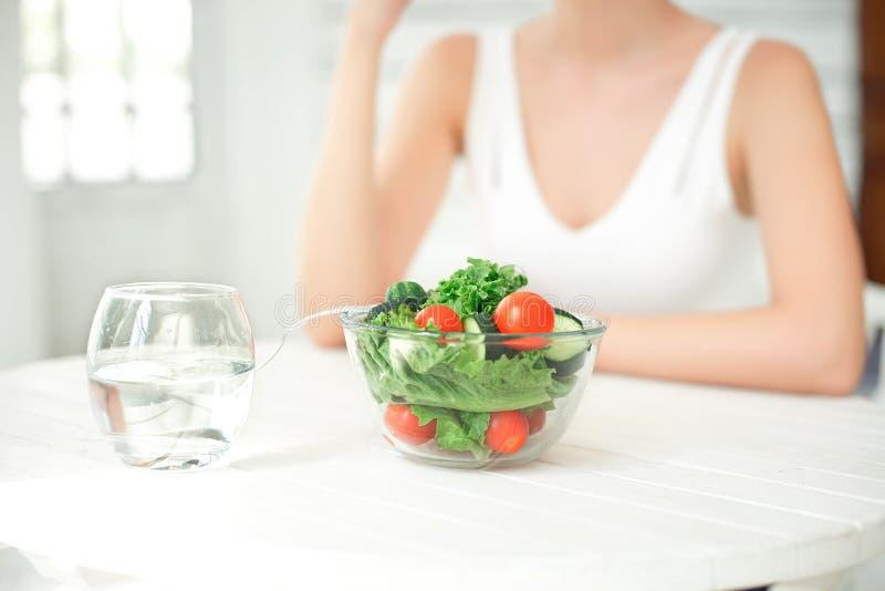 吃健康沙拉的美丽的适合妇女 免版税库存照片