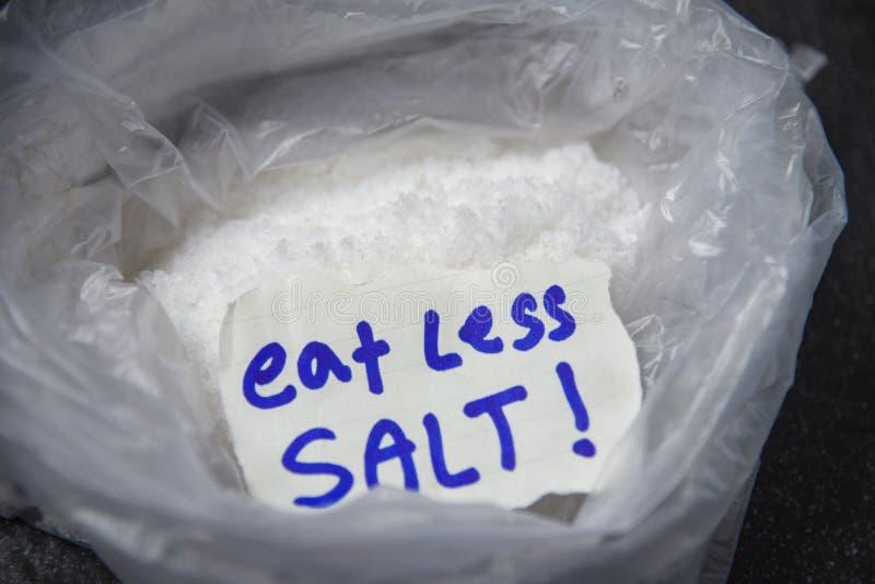 吃健康盐概念堆的较少盐在塑料袋背景中 免版税库存照片