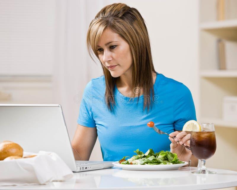 吃健康膝上型计算机午餐键入的妇女 免版税库存图片
