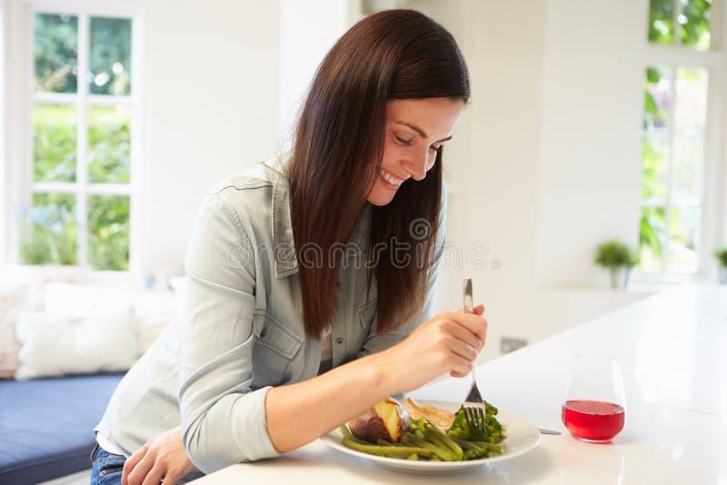 吃健康膳食的妇女在厨房里 免版税库存图片
