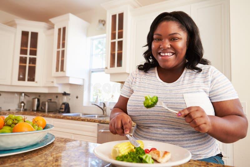 吃健康膳食的超重妇女在厨房里 免版税图库摄影