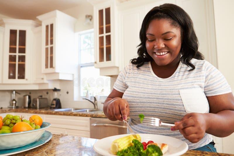 吃健康膳食的超重妇女在厨房里 免版税库存照片