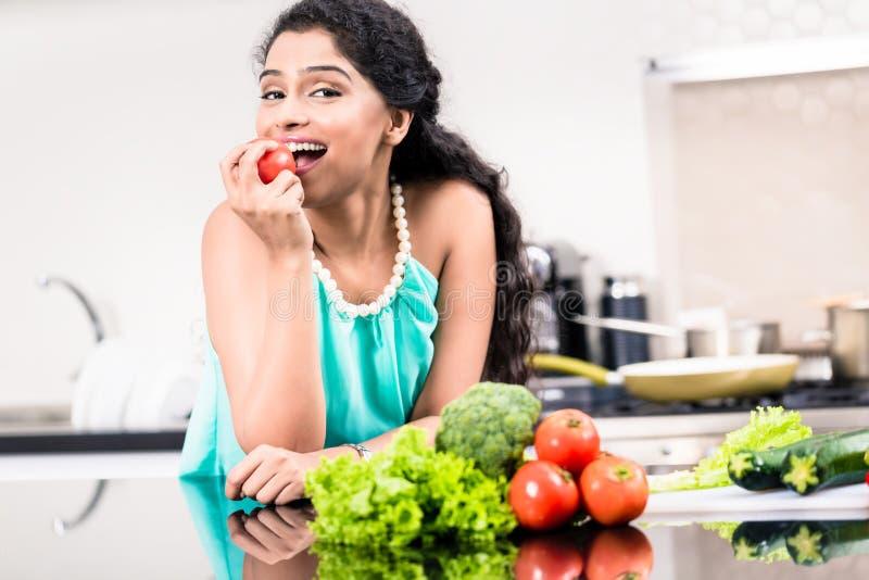 吃健康苹果的印地安妇女在她的厨房里 免版税库存照片