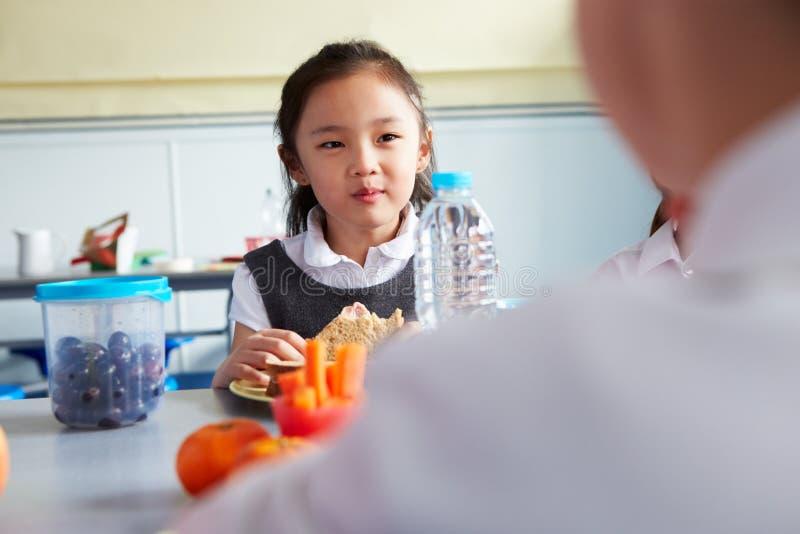 吃健康被包装的午餐的女孩在学校食堂 图库摄影
