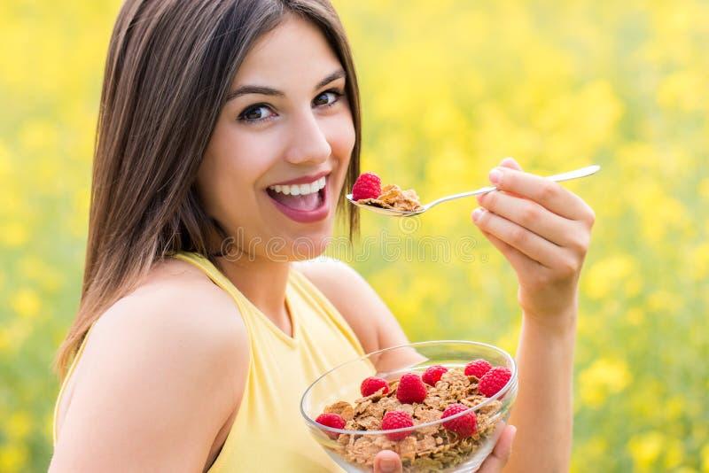 吃健康谷物早餐的逗人喜爱的女孩户外 库存图片