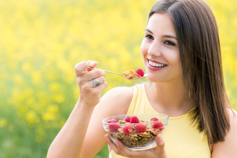 吃健康谷物的逗人喜爱的少妇户外 库存照片